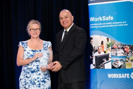 Glenda McMurtrie, occupational safety and health manager at Juniper, accepts the finalist certificate and winner's trophy from Tony Krsticevic, parliamentary secretary to the minister for Commerce.